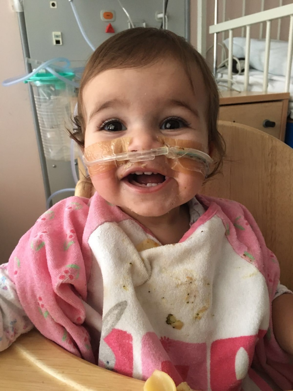 Baby sitting in chair and smiling in hospital while receiving treatment