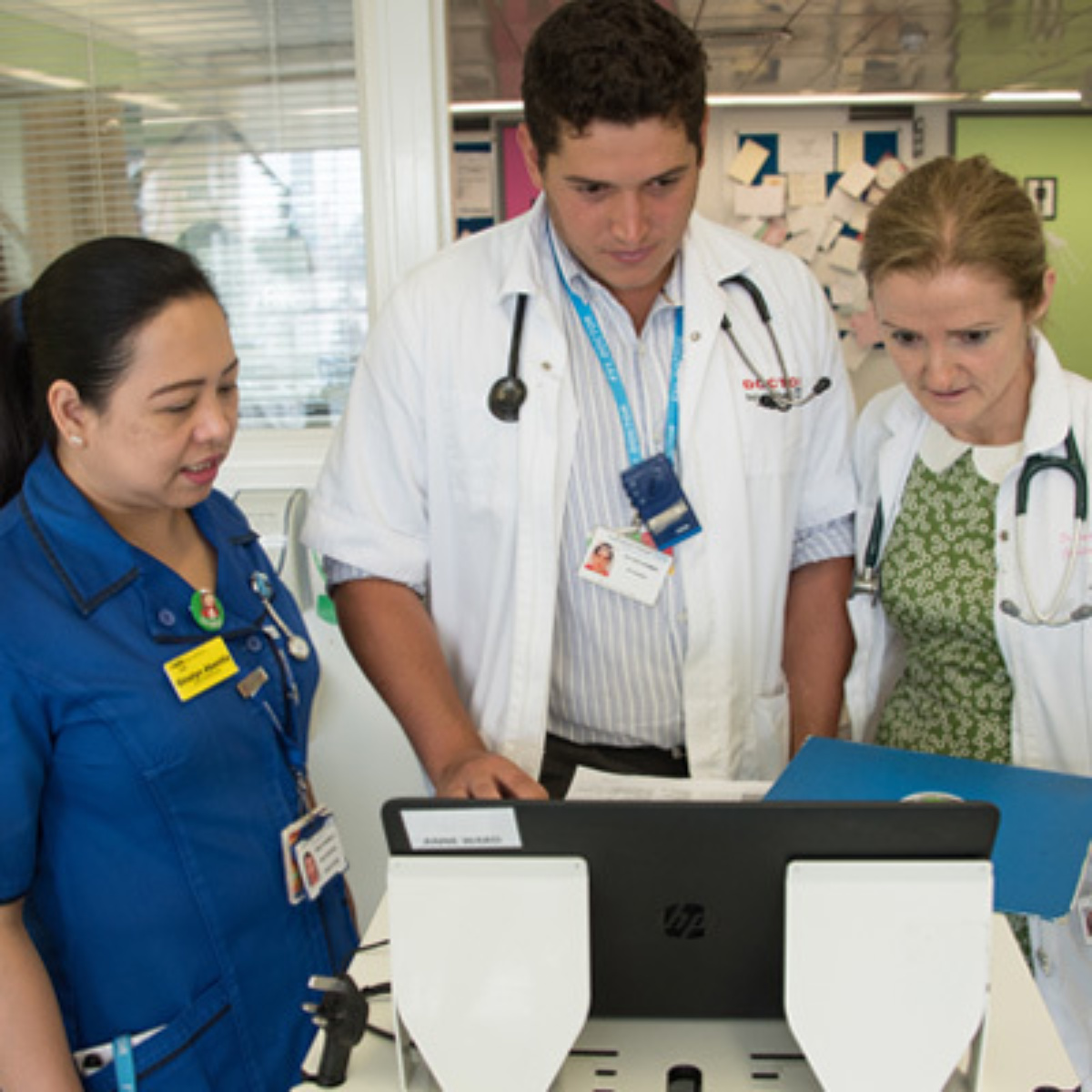 Doctor with nurses in a hospital ward, assessing patient's chart