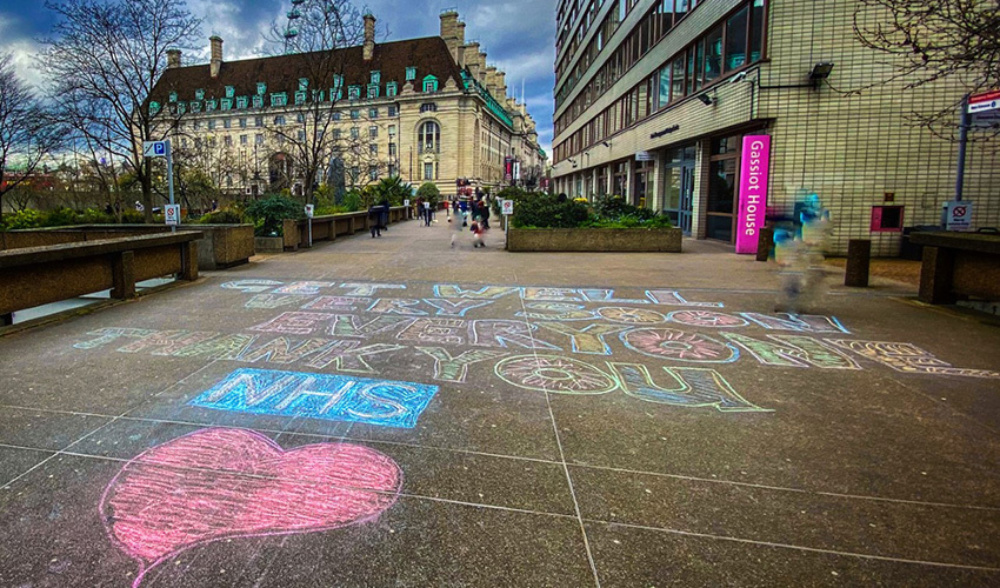 Pavement with colourful writing saying 'thank you to the NHS' with people walking towards it