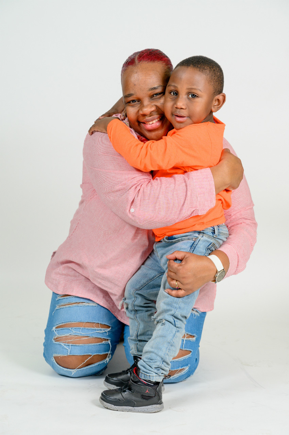 A young child hugging his mother in front of a plain white background