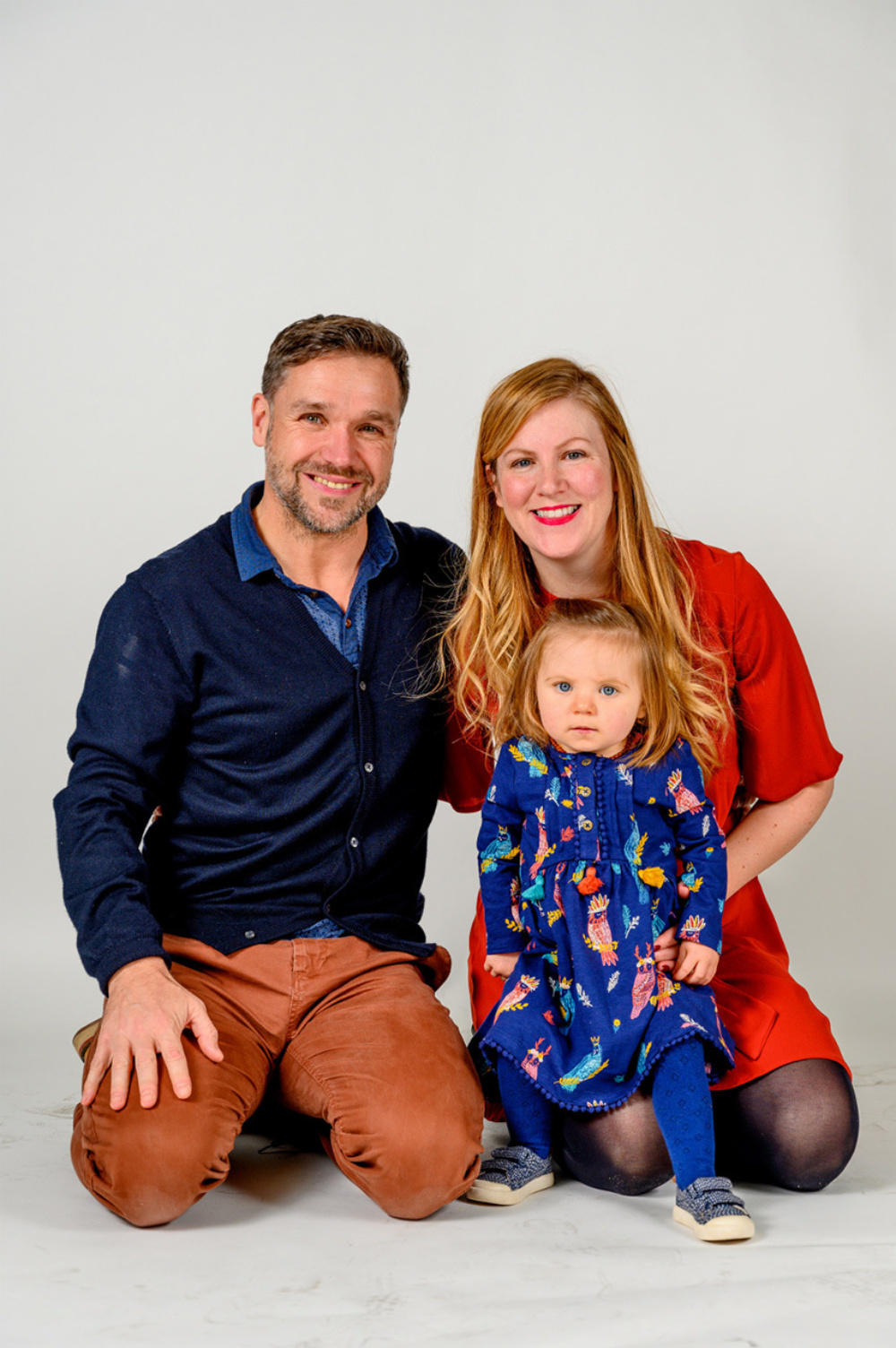 A couple posing with their child in front of a white background