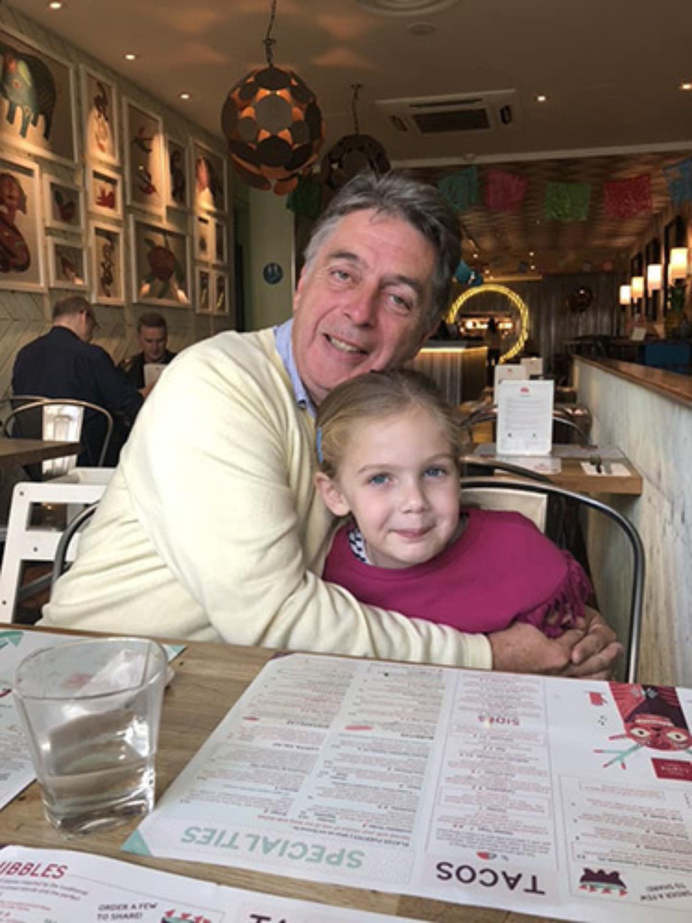 Grandfather Julian, holding his granddaughter, Maddison, in a restaurant