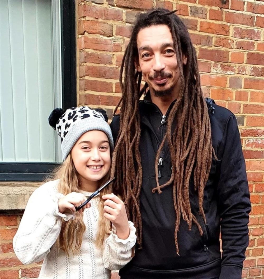 Molly Nana pretending to cut off her dad's 92cm-long dreadlocks, which he will shave to raise money for Evelina London.