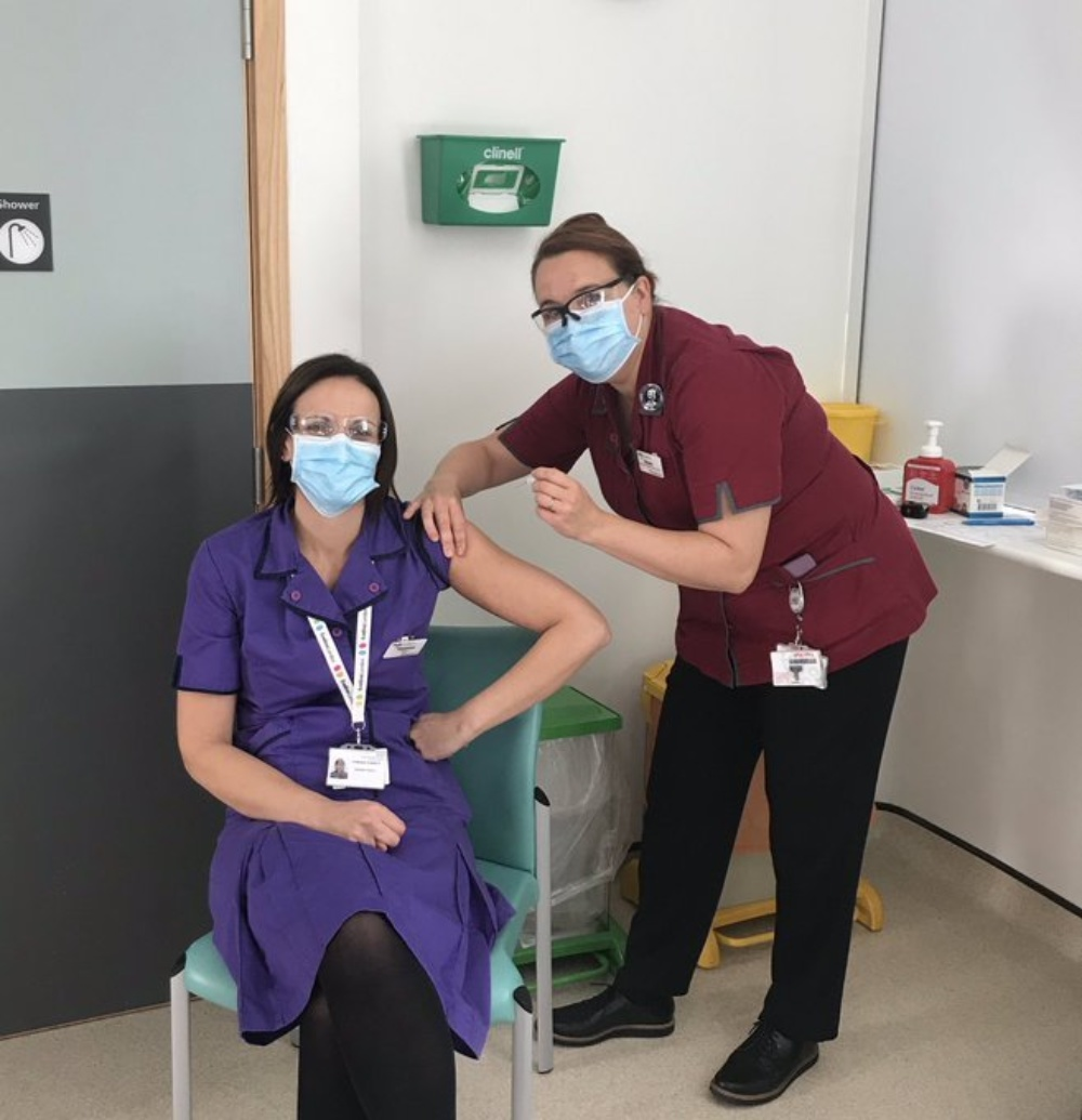 Shona administering a flu jab to her colleague Vanessa