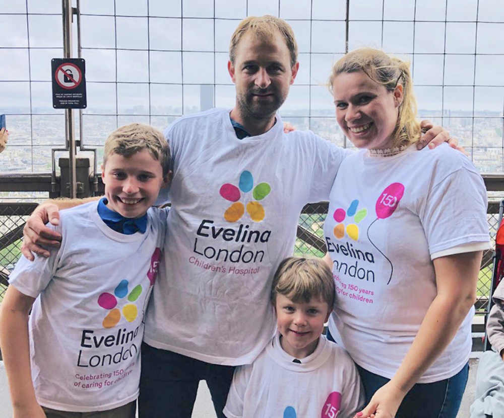 Two boys with their mother and father, stood together, all smiling in their Evelina London t-shirts