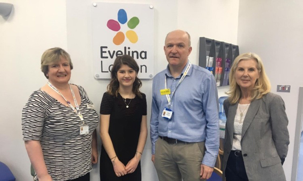 Four people standing in front of Evelina London sign in a ward at Evelina London. Evelina London's Grainne Walsh, Cissy Adamou, John Simpson, and Cissy's mother, Jo.