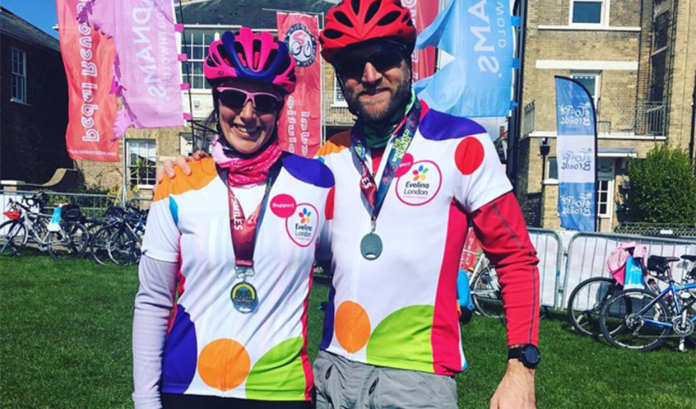 Smiling couple, Sarah and Ian, in Evelina London branded sports wear, wearing medals