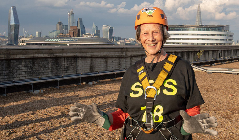 A lady on top of a hospital roof in a helmet and harness, ready to abseil down the building