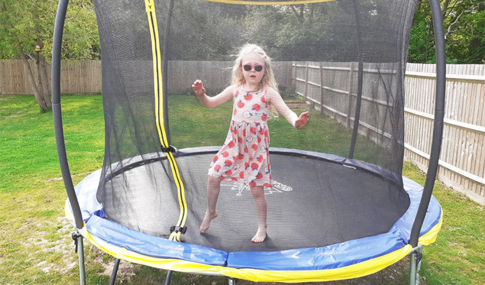 Young girl in a summer dress with sunglasses bouncing on a small trampoline, outdoors in her family garden