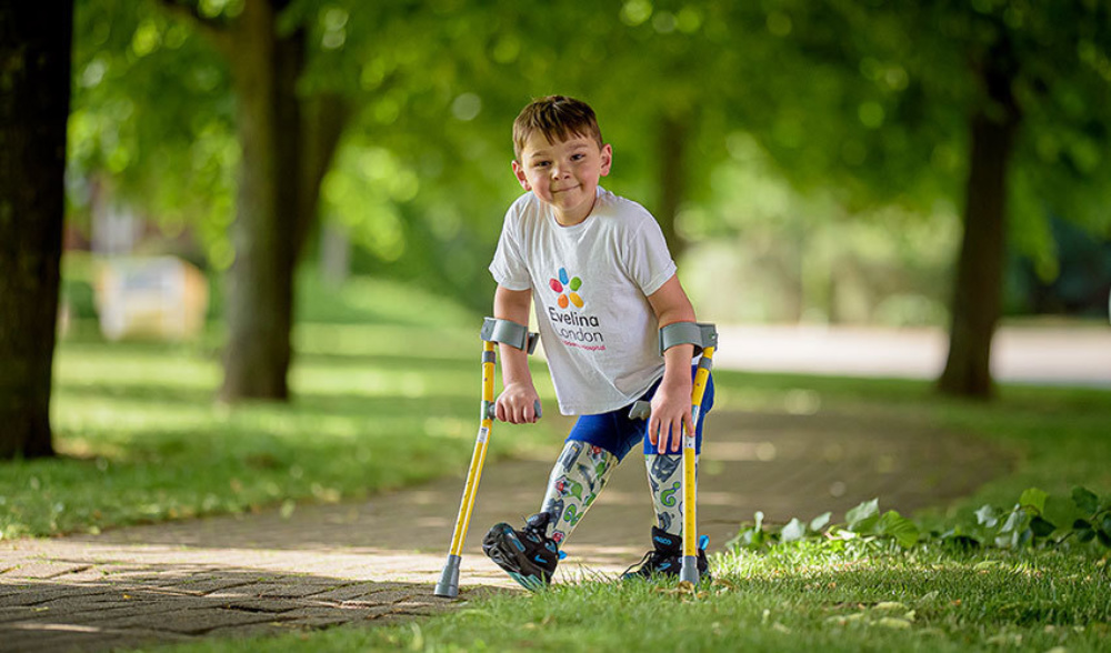 A young boy, walking in the park with crutches and smiling in an Evelina London t-shirt