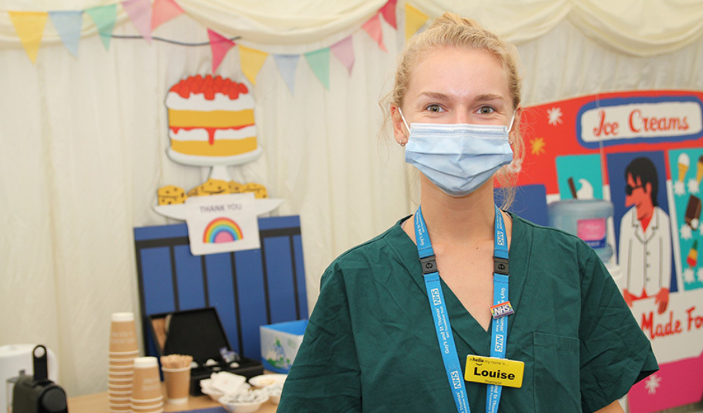 Lady in medical clothing and face mask, in front of table with refreshments