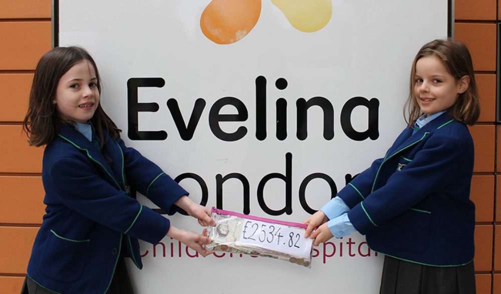 Two school girls holding a fundraising cheque in front of the Evelina London sign outside the hospital