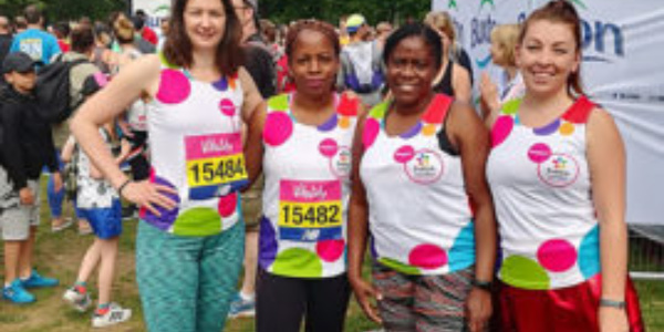 Four ladies, stood in a row, with Evelina London running tops and running shorts, in a park at the finish of a race