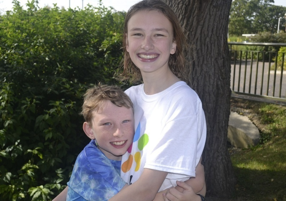 smiling girl wearing evelina t-shirt hugging boy, with tree in the back