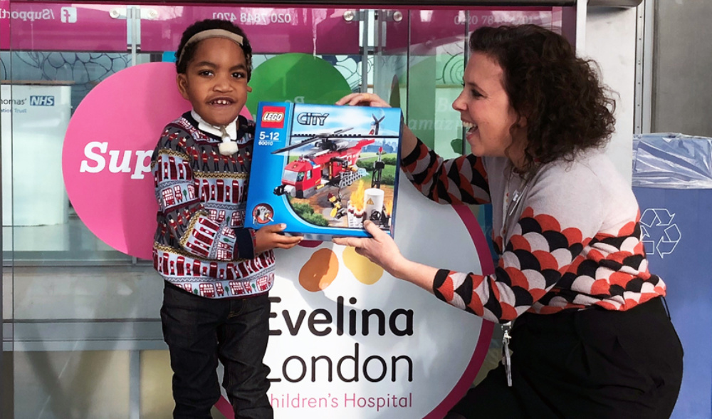 a boy and a smiling lady presenting logo box with evelina logo behind them