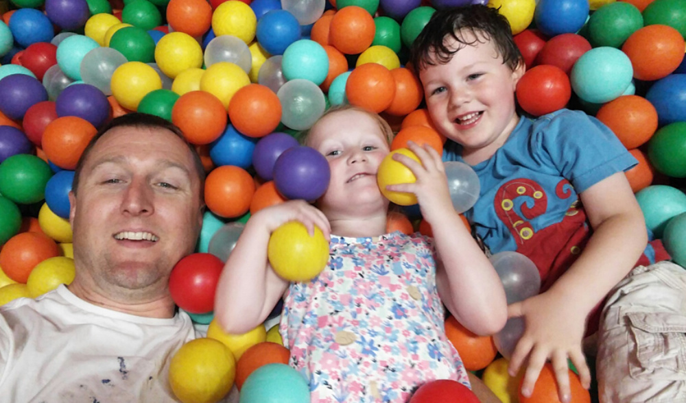 happy dad with his two children in the colourful ball pool