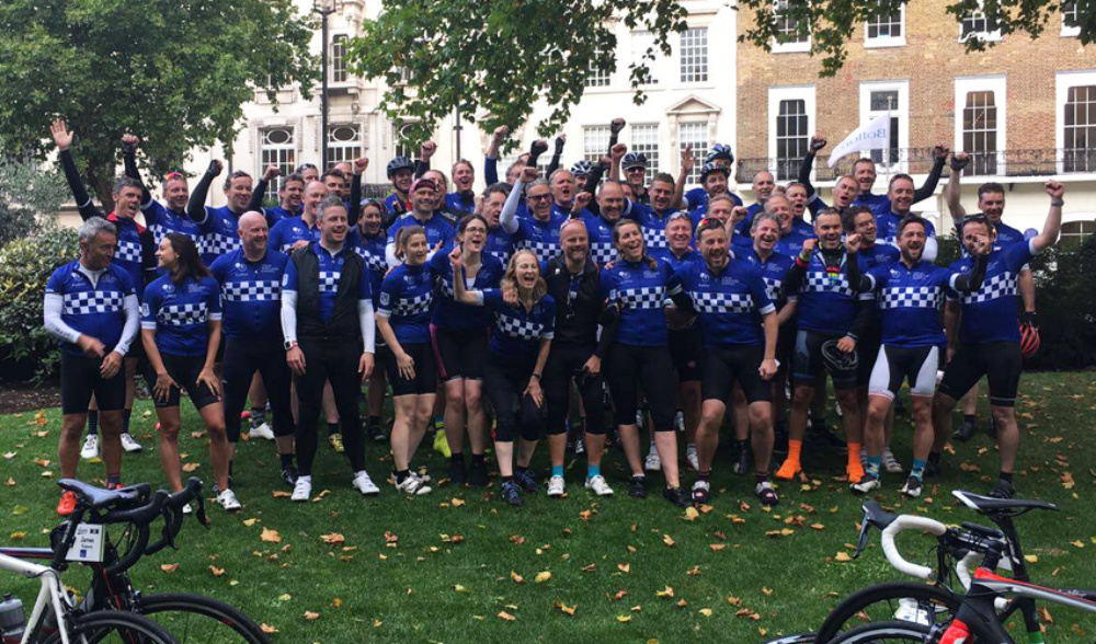 team of fundraisers in cyclist clothes on the lawn with the building behind and a couple of bikes in the front