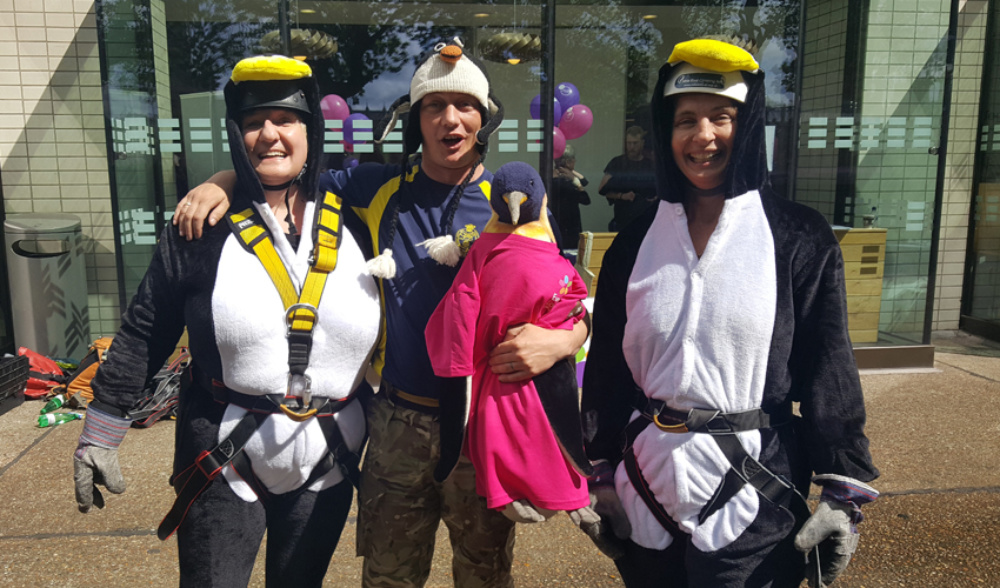 three happy fundraisers wearing penguins costumes and abseil harness holding penguin toy in the middle