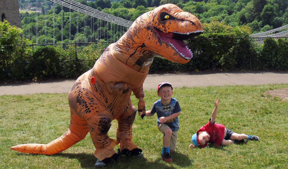 two boys, one laying on the lawn, the other holding hand of an orange human size trex dinosaur with the bushes in the background