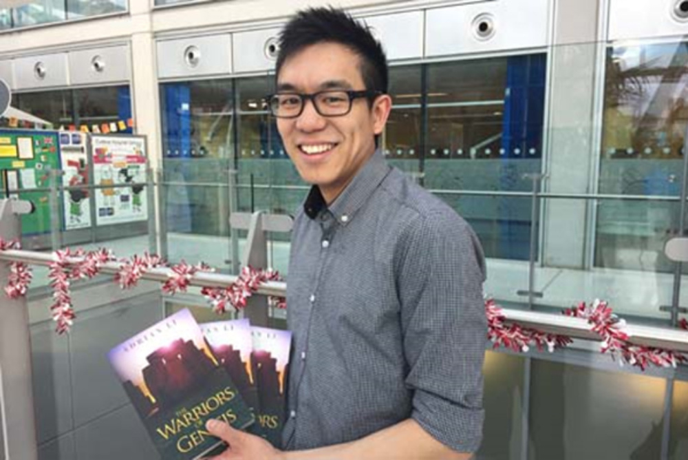 author, dr adrian li, holding his books titled warriors of genesis in the front of a building
