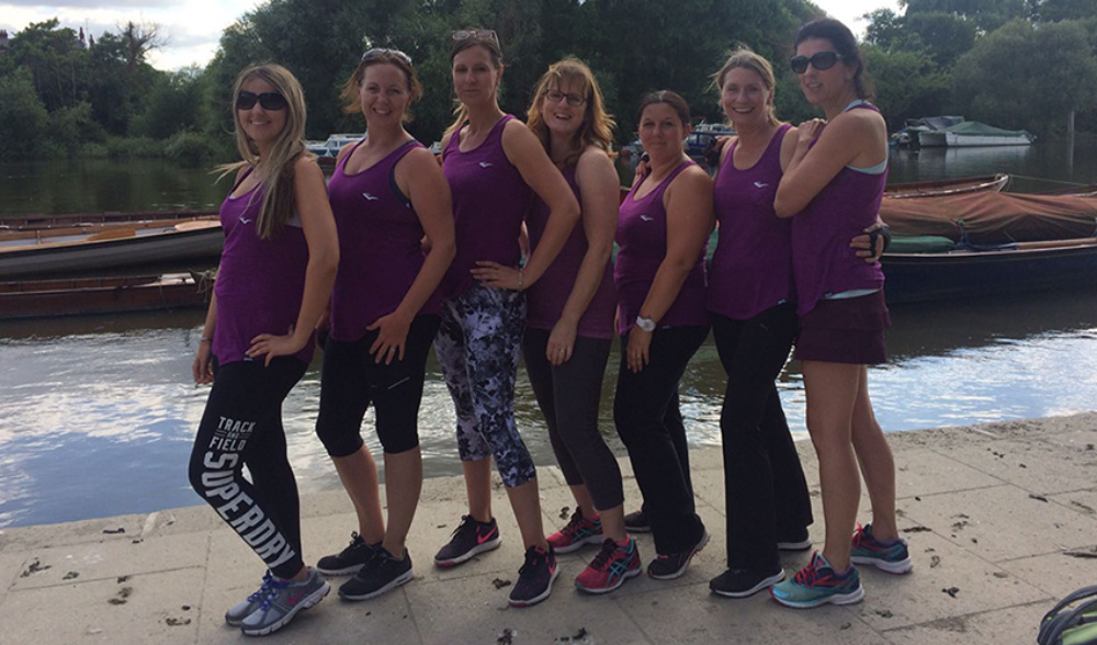 team of ladies in purple sportswear posing outdoor with the lake in the background
