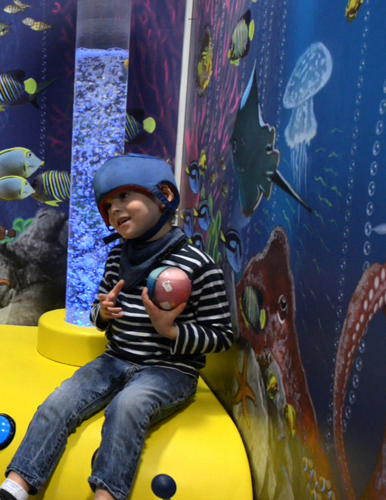 Boy sitting in sensory room holding ball