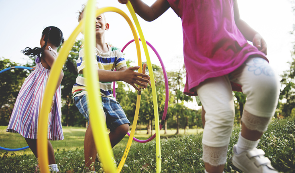 Three children playing with hula hoops outside
