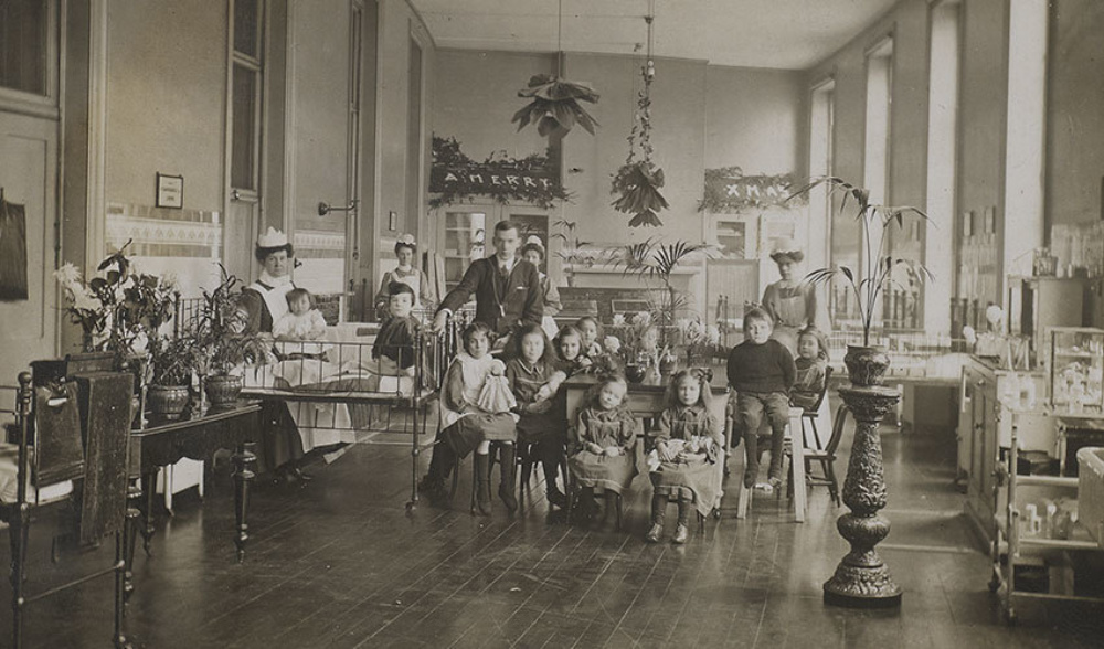 Hospital ward from turn of the 20th century, with several young patients, a doctor and nurses.