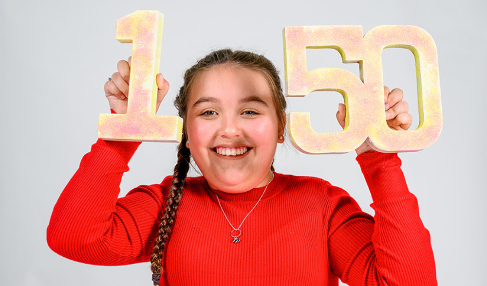 Young girl smiling, while holding a cut out of the number 150