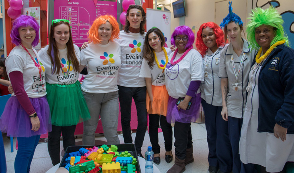 Eight people, stood relaxed in a row, dressed in colourful clothing with bright wigs and Leis