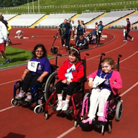 three young girls in wheelchairs at sports track
